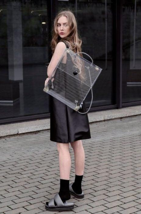 Chica llevando mochila transparente a espaldas