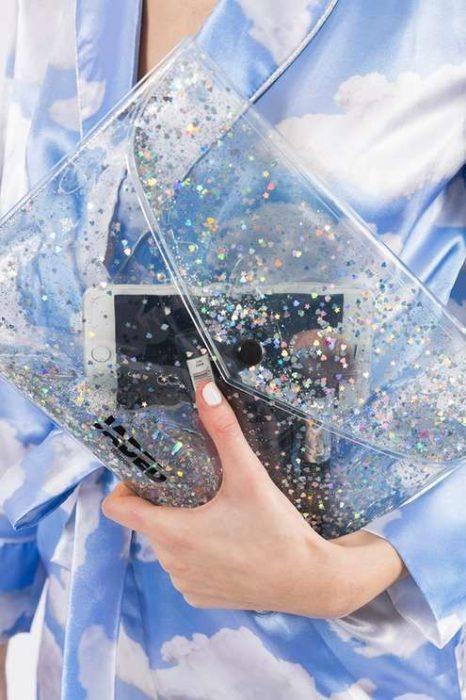 Mujer sosteniendo cartera transparente con glitters