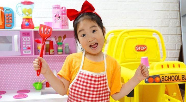 Boram sosteniendo una espátula de juguete junto a su cocina de fantasía