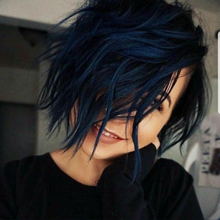 Chica cubriendo su rostro con su cabello corto en tono azul marino