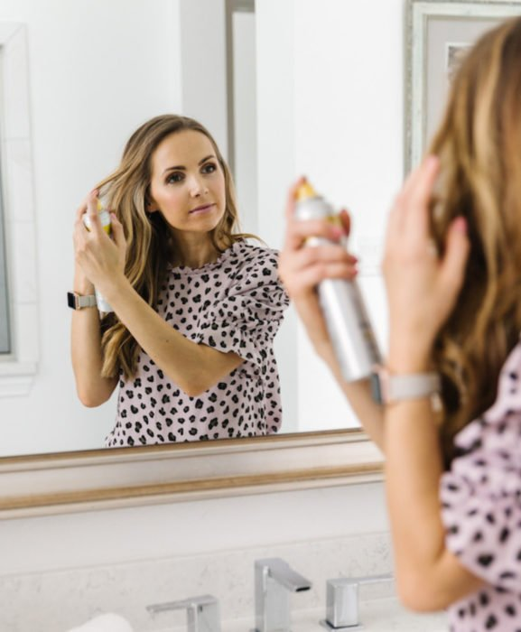 Mujer rubia de cabello largo aplicándose champú seco en spray frente al espejo