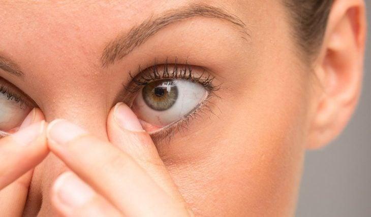 primo piano dell'occhio di una donna che lo graffia con un dito