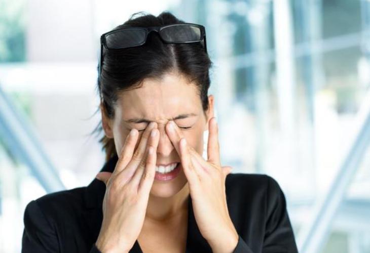 mujer vestida de negro con lentes sobre su cabeza se frota los ojos
