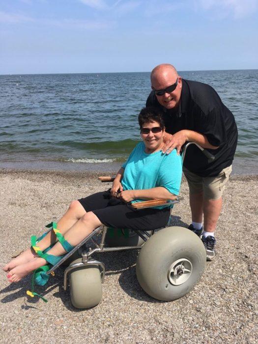 Persona que no puede caminar usando una silla especial para la playa