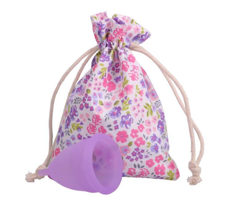 copa menstrual de color violeta con una bolsa floreada a un lado