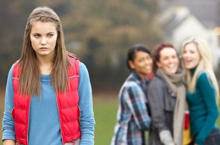 primer plano de una joven de blusa azul y chaleco rojo, atrás otras tres se burlan de ella