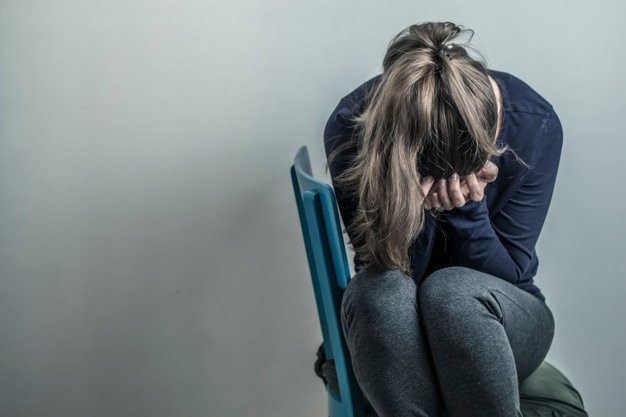 una mujer sentada tiene su cara entre sus manos agachada