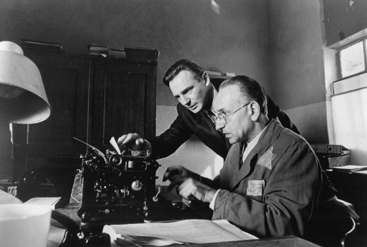 Datos sobre películas; La lista de Schindler con Liam Neeson; dos hombres con traje escribiendo en una máquina de escribir