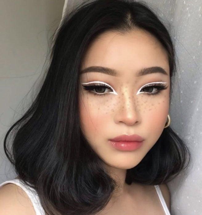Chica mostrando su delineado de color blanco sobre los parpados