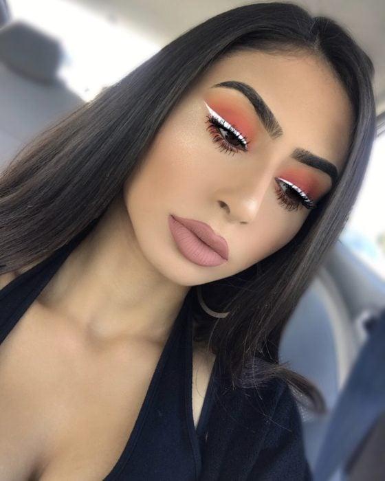 Chica con un delineado de color blanco sobre sus sombras de color naranja