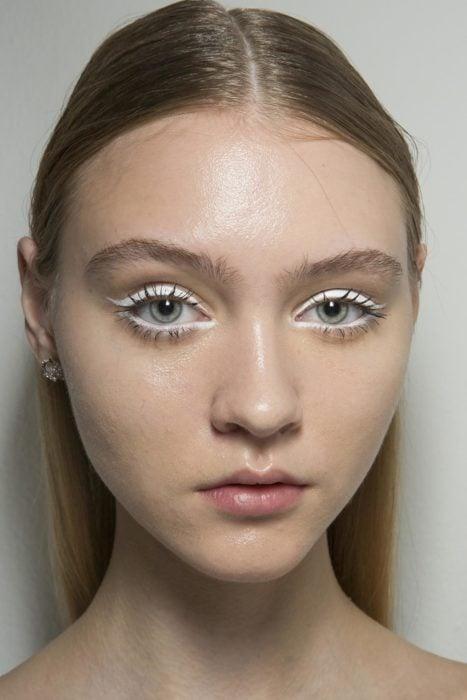 Chica con un delineado de color blanco sobre el parpado y bajo el lagrimal