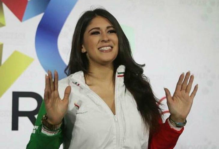 Paola Pliego Lara en un podium levantando los brazos