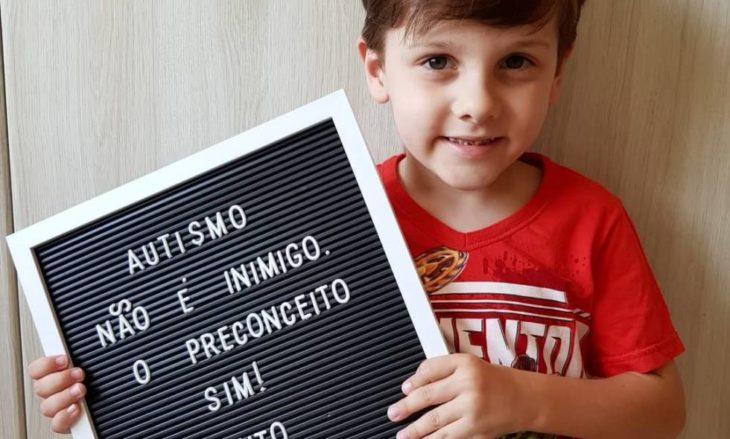 Rafael Mayer el niño autista sosteniendo un letrero