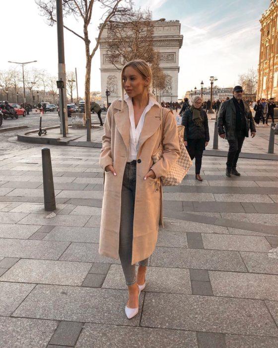 Influencer Elle Darby pide alojamiento gratis a hotel; mujer rubia en el Arco del Triunfo en París