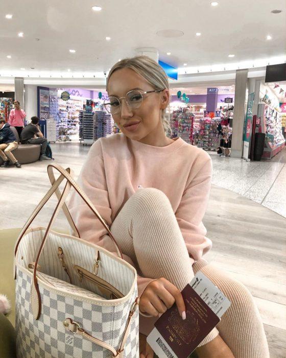 Influencer Elle Darby pide alojamiento gratis a hotel; mujer rubia con lentes de aumento en aeropuerto con VISA en la mano