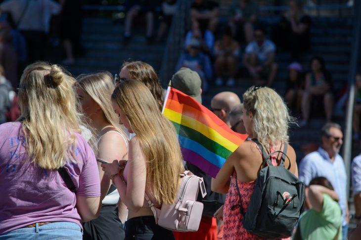 varias mujeres durante una marcha llevan la bandera del orgullo gay