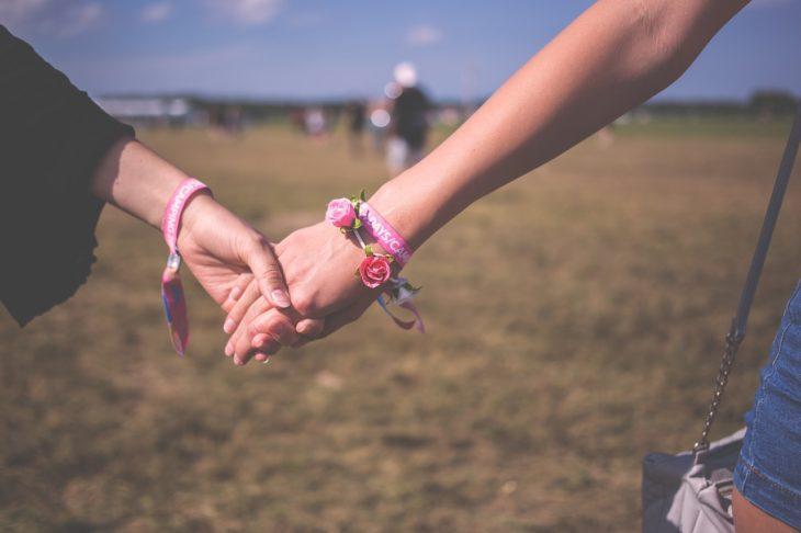 las manos de dos mujeres unidas y un campo de fondo