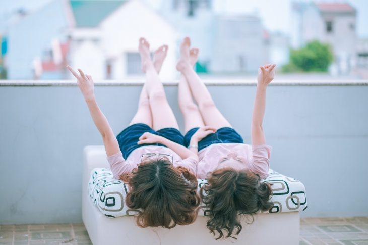 dos mujeres acostadas en una cama con playera rosa y short azul con las piernas sobre una barda y levantando un brazo cada una