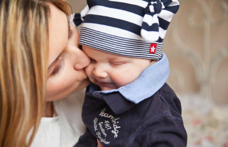 una mamá besa a su bebé con gorro azul con blanco