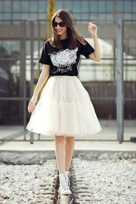 Chica a mitad de avenida modelando su outfit urbano con falda de tul