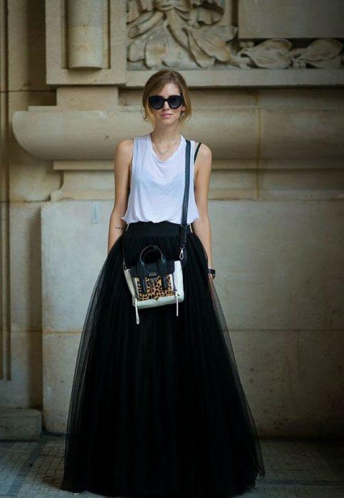 Chica con falda de tul larga, bolso cruzado y gafas oscuras modelando