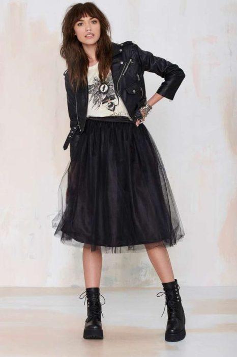 Chica con falda de tul en negro, chaqueta de cuero y botas de piel