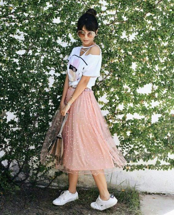 Chica modelando una falda rosa de tul con puntos blancos y bolso en plata