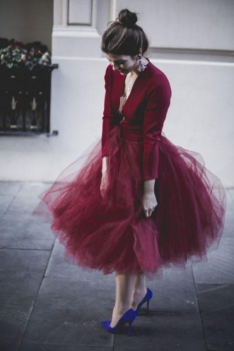 Chica con outfit color vino mirando hacia abajo para observar el piso