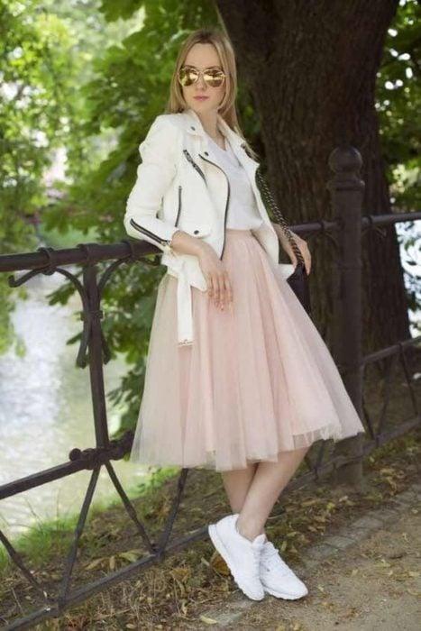 Chica recargada en una cerca de madera, usando falda de tul y tenis