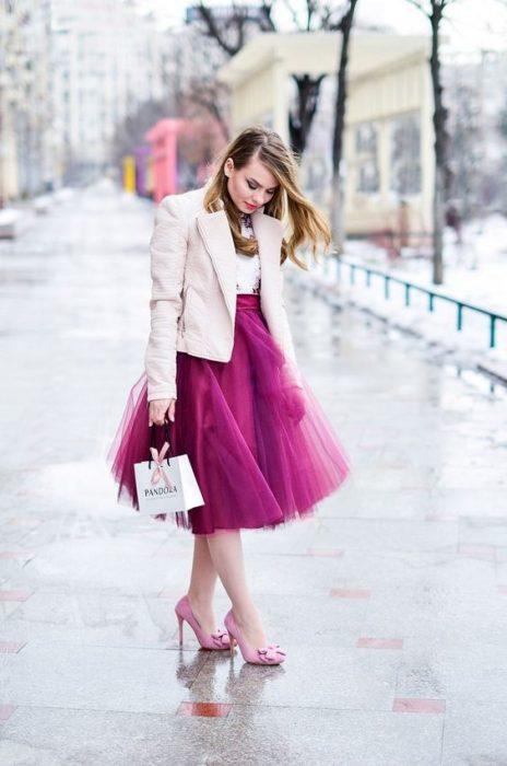 Chica con falda de tul en tono rosa fuscia, modelando su ropa y zapatos del mismo color