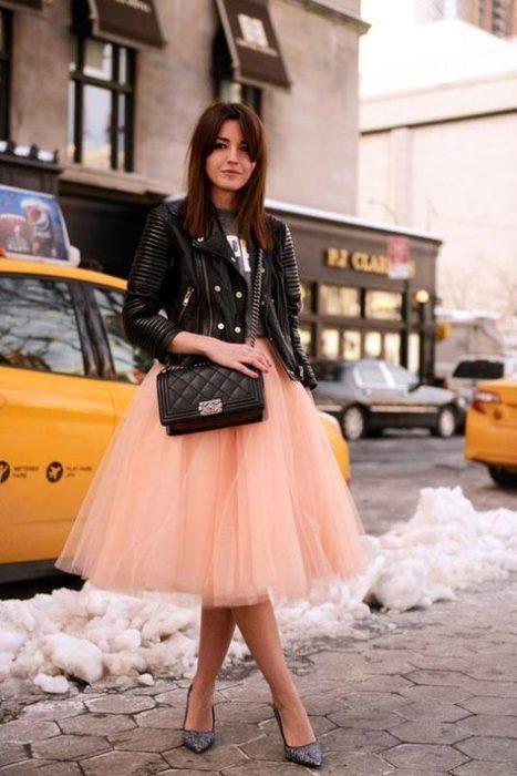 Chica modelando su falda de tul en tono color melón con chaqueta de cuero en negro