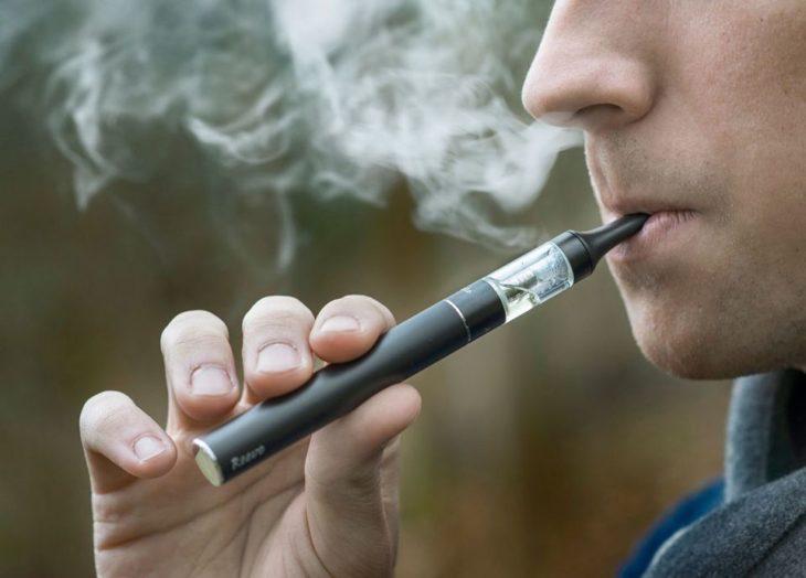 cara de un joven fumando con un cigarrillo electrónico