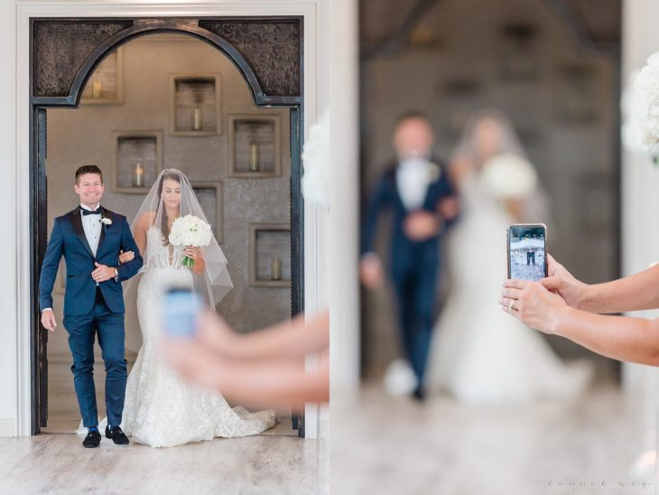 Fotógrafa de bodas Hannah Mbalenhle Stanley; novia con su vestido blanco de la mano de su papá entrando a la iglesia, chica se atraviesa con su teléfono para tomar foto
