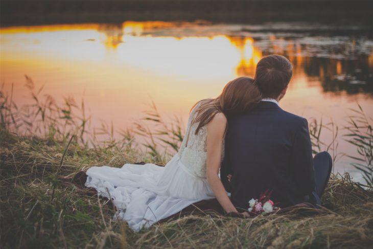 Sesión de fotos de boda; pareja de recién casados sentados junto a un lago