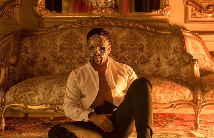 Mario Casas en la serie instinto sentado en una cama y usando una máscara