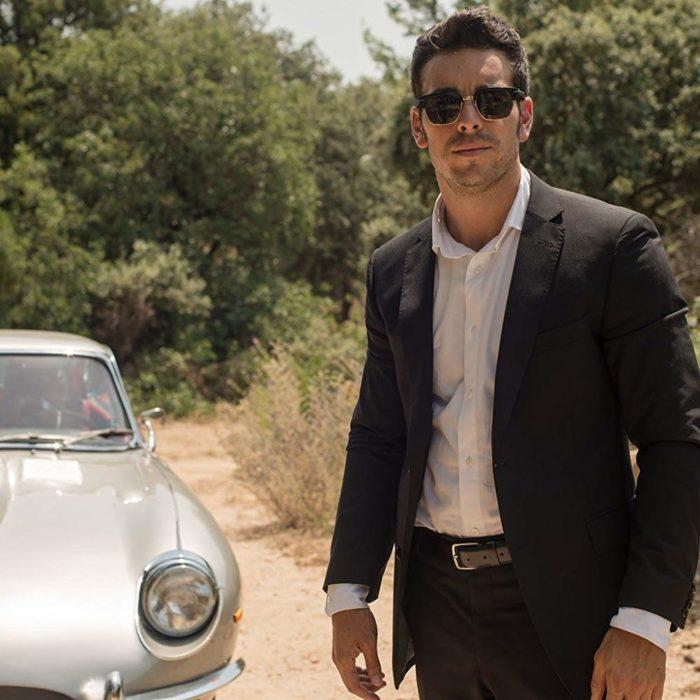 Mario Casas en la serie de Movistar 'Instinto'. Parado frente a un auto mientras mira hacia la nada
