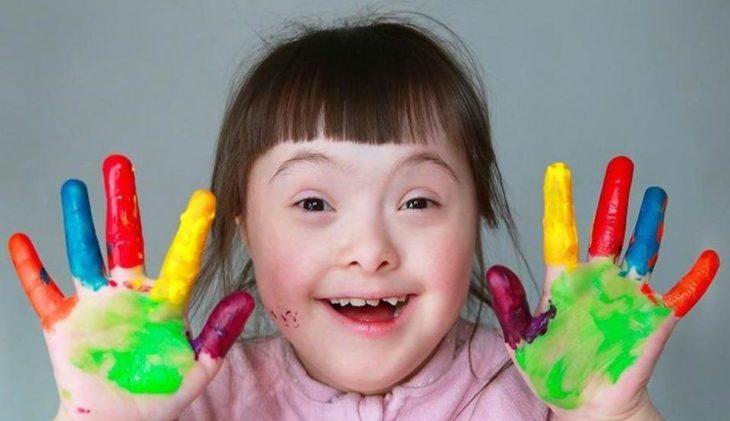 una niña con síndrome de Down muestra sus manos pintadas de colores