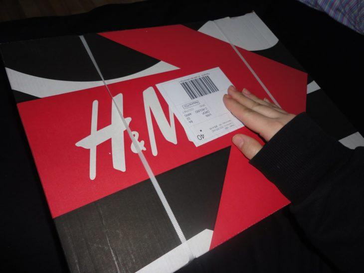 una mano revisa la etiqueta de un envío a domicilio de H&M