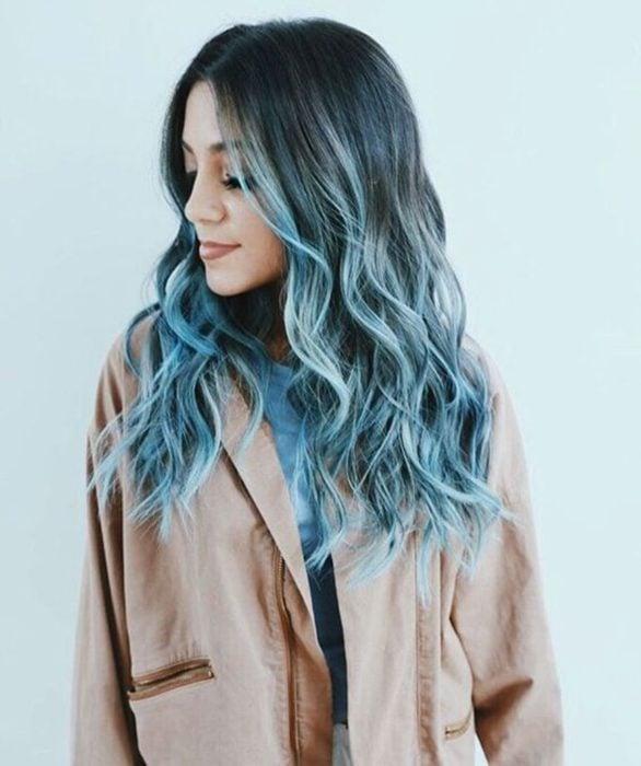 Chica de perfil, modelando su cabello en ondas con balayage en azul