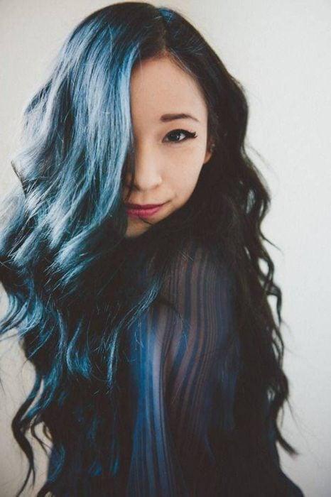 Chica cubriendo su rostro con su cabello largo con mechas en azul