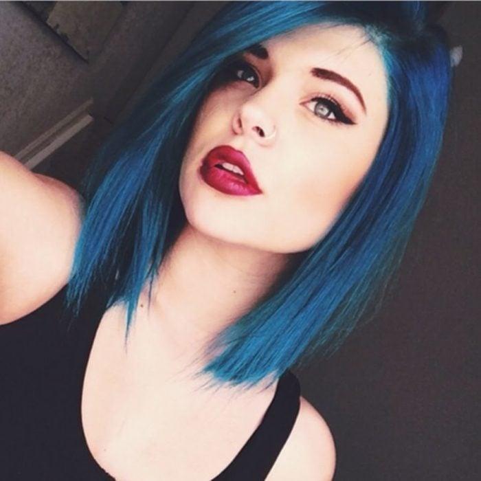 Chica tomándose una selfie para mostrar su cabello corto en azul eléctrico