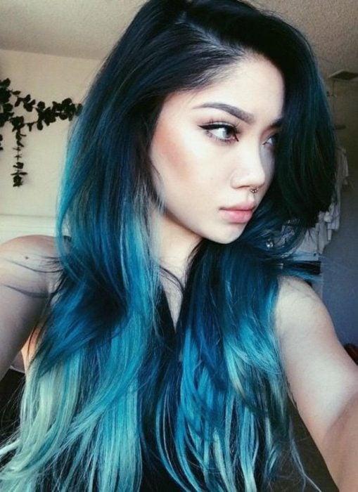 Chica tomándose una selfie de perfil, mostrando su cabello azul eléctrico y aqua