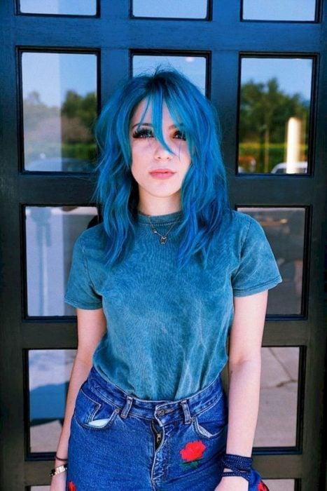Chica posando frente a una puerta de cristal, mostrando su cabello azul eléctrico