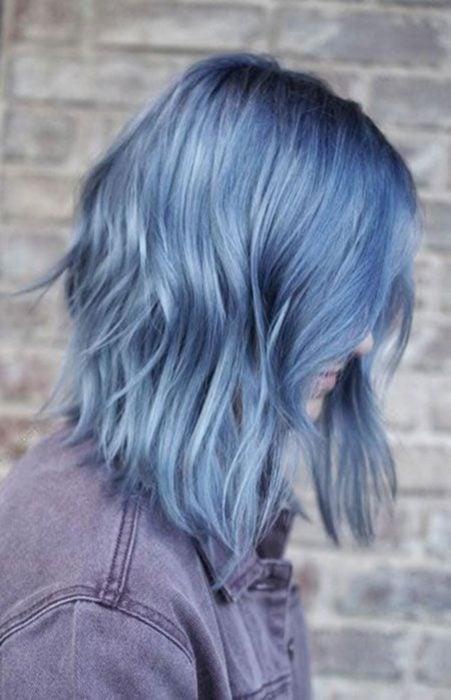 Mujer de perfil, cubriendo su rostro con su cabello color azul cielo