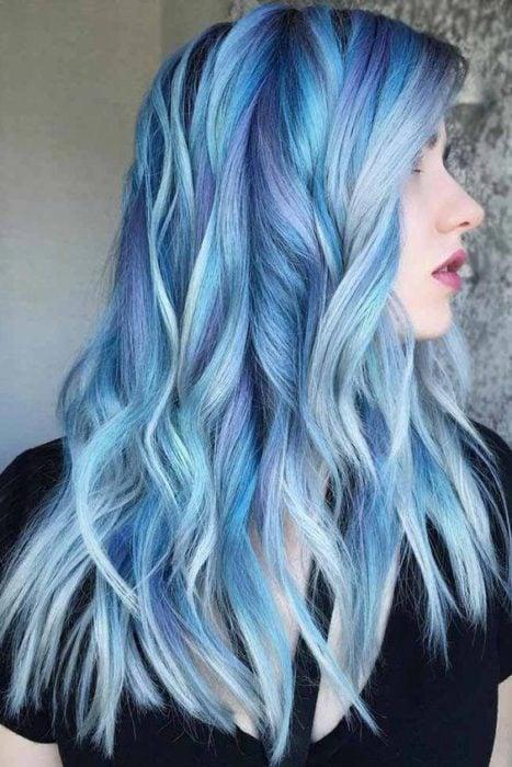Chica de perfil, cubriendo su rostro en tono azul cielo y lila