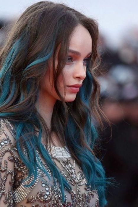 Chica de perfil, mostrando su cabello largo en tonos castaño y azul aqua