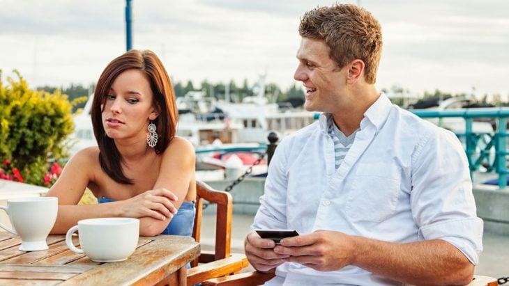 Mujer volteando a ver el celular de su pareja porque intuye que le es infiel
