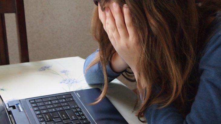 una mujer frente a una computadora se tapa la cara con las manos