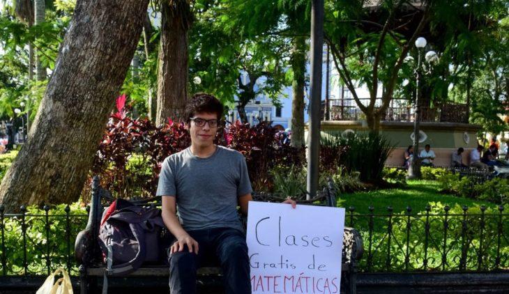 Axel Roberto Ruíz Ortega sentado en una banca de un parque dando clases de matemáticas