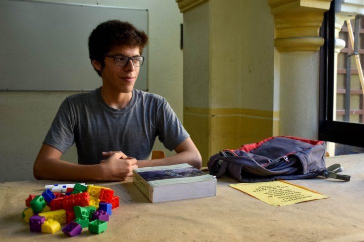 Axel Roberto Ruíz Ortega dentro de una biblioteca revisando sus apuntes